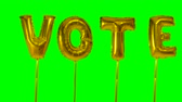 投票 : Word vote from helium golden balloon letters floating on green screen