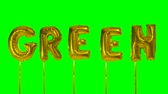 メッセージ : Word green from helium golden balloon letters floating on green screen