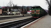 wagons : Ukraine, Yaremche - November 20, 2019: the railway station, a train passes by, in the background mountains. Passengers leave the train on the platform of a small station in a sparsely populated city.