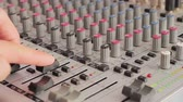 tumblers : Sound engineer working with an analog audio mixer. Fingers hand man to raise and lower the fader, turn the handle and insert the plug into the socket on the mixer. Stock Footage