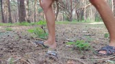 utilization : A man stepped on a plastic bottle in a pine forest. People throw garbage in the forest.