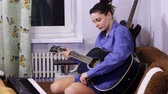 честный : Young beautiful girl learning to play the guitar at home.