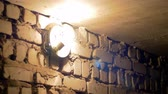 amper : Filament Bulb Lights Up on a Stone Wall