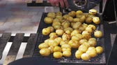 cooking : Young potatoes prepare on a grill. Hand Using Tongs For Turning potatoes on the Barbecue Stock Footage