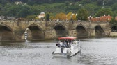bridge across the river : People walk along the old Prague Bridge and Boat Floating on the River Vltava