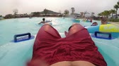 bronzeado : Pov view of Man floating on inflatable circle in the pool with artificial waves