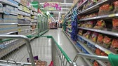 grocer : Shelves with goods in supermarket. Grocery shopping from view of a shopping cart. Thailand.