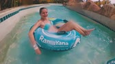 inflável : Guy with a girl on an inflatable circle is swimming in the pool. POV. Aqua Park