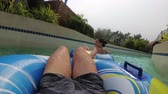 pool deck : Guy with a girl on an inflatable circle is swimming in the pool. POV. Aqua Park