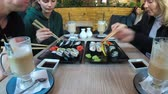 zastawa stołowa : The family at the restaurant eating a large sushi set and drinking latte sitting at a stylish table. Time Lapse Wideo