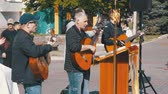 cent : Street musician band playing on the acoustic guitars. Slow Motion Stock Footage