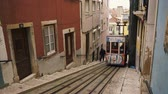Lisbon, Portugal - March 25th, 2013: Tram car driving uphill out of a tunnel on narrow gauge rails through a narrow alley in Lisbon, Portugal Dostupné videozáznamy