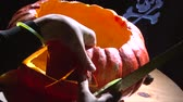 stabbing : Pumpkin carving with knife, cutting out the eye against scull at dark background Stock Footage