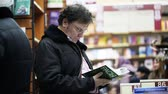 MOSCOW - FEBRUARY, 21: Professor studies the book about races in bookstore in Moscow Stok Video