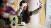Young beautiful girl makes selfie in a cafe after fruit tea Stok Video