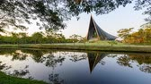 Nakhon Pathom, Thailand - 18 Dec, 2019 : Zoom in time lapse Prince Mahidol Hall building of Mahidol university with reflections of the sun on the lake view