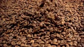 beállítás : The roasted coffee beans fall on the table. Slow motion video. Preparation of morning coffee for breakfast.