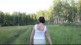 vislumbre : Woman walks along a forest road summer day.