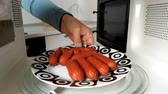 микроволновая печь : Woman puts sausages in the microwave. Стоковые видеозаписи