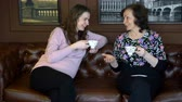 tea time : Mother and pregnant daughter in a bright room are sitting on the couch, drinking hot tea and talking about the secrets of women