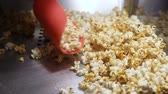çatırtı : Woman picking up a shovel fried popcorn from the popcorn machine Stok Video