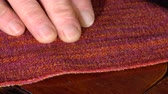 numaracı : The seamstress pulls out scraps of thread from the fabric. Close-up