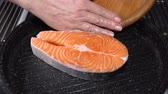 cookware : Raw salmon steak put in the pan. Slow motion