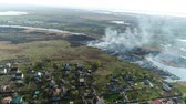 above fire : Flying over the river with reeds. Fire reed on the river near the village. Aerial survey Stock Footage
