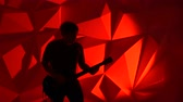 slider bar : The musician plays the guitar. Guitarist silhouette on red background. Background photography in a photo studio