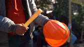 asa : Workers baton with protective orange helmet for protests. Slow motion. Video with sound