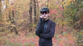 major : Young professional male cyclist talking on phone before workout on bike in fall park. Attractive nervous cycling guy speaking on phone in autumn forest before training. Slow motion