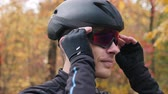 ciclismo : Motivated young cyclist athlete in black helmet puts on sport glasses before workout on bike. Extra close up view. Cycling training in fall park. Man cycling. Triathlon concept. Slow motion Stock Footage