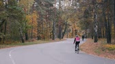 ciclismo : Group of male and female cyclists in cycling apparel riding on road bicycle in empty autumn park. Young sportive women and men hard training on bikes in fall forest Stock Footage