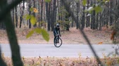 ciclista : Young good-looking professional cyclist in cycling apparel and helmet trying to stand in track on road bike. Stylish young male triathlete riding on bicycle in autumn park Vídeos