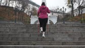 snellente : Nordic Walking. Young adult doing nordic walking exercises in city going up the stairs. Cardio outdoor activity