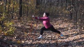 baston : Stretching exercises with nordic walking poles before training in city autumn park. Weight loss concept