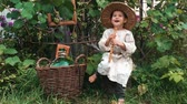 apito : Happy funny little boy in straw hat sitting in garden, playing on music instrument and laughing. Charming cute child smiling Stock Footage