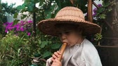 assobio : Funny little child in straw hat trying to play on flute with green garden on background. Happy boy playing on music instrument