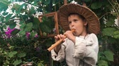 assobio : Portrait of happy funny little boy diligently trying to play on tin wistle. Cute charming baby boy playing on flute