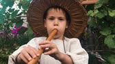 assobio : Close up view of little charming boy in straw hat playing on wooden music instrument in green garden. Happy child plays on flute
