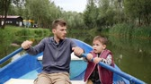 canoe : Young father and his little son float together in boat among green trees. Happy family having fun at the weekend in park on lake. Little son talking to his father. Daddy spending time with son on lake
