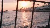 키프로스 : Sunset through lattice. Pink sunset through fence. Beautiful sea sunset. Pink sunset on marina. Tourist promenade on sunset. Pink sunset rays. Beautiful sunset rays. Sunset path.
