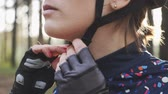 ciclista : Young cyclist girl tightens harness on the helmet before the bicycle ride. Cycling concept. Slow motion Vídeos
