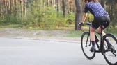 джерси : Sportive fit female cyclist pedalling out of the saddle in the park. Hard training on bicycle. Road cycling concept