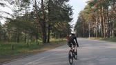 ciclista : Fit sportive cyclist sprints uphill out of the saddle. Training on road bicycle. Back side follow shot. Vídeos