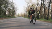 bisiklete binme : Strong confident triathlete riding bicycle in the park. Back follow shot. Triathlon concept. Stok Video