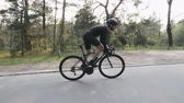 ciclismo : Riding a bicycle side follow view. Bearded man in black outfit on bicycle in the park. Out of the saddle pedaling. Slow motion