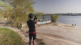 major : Cyclist wearing black outfit, helmet and sunglasses holds his cellphone camera and takes pictures of city river. Male sportsman with phone camera. Slow motion