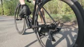 racefiets : Strong leg muscles of cyclist pedaling on bicycle. Follow camera shot of biker legs in motion on bicycle. Stockvideo