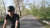 주기 : Relaxed athletic fit cyclist riding a bicycle in the park. Front follow shot. Bearded cyclist wearing black outfit easy ride on bike.